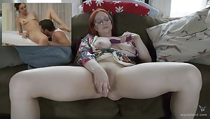Busty redhead watches porn coupled with masturbates with toys